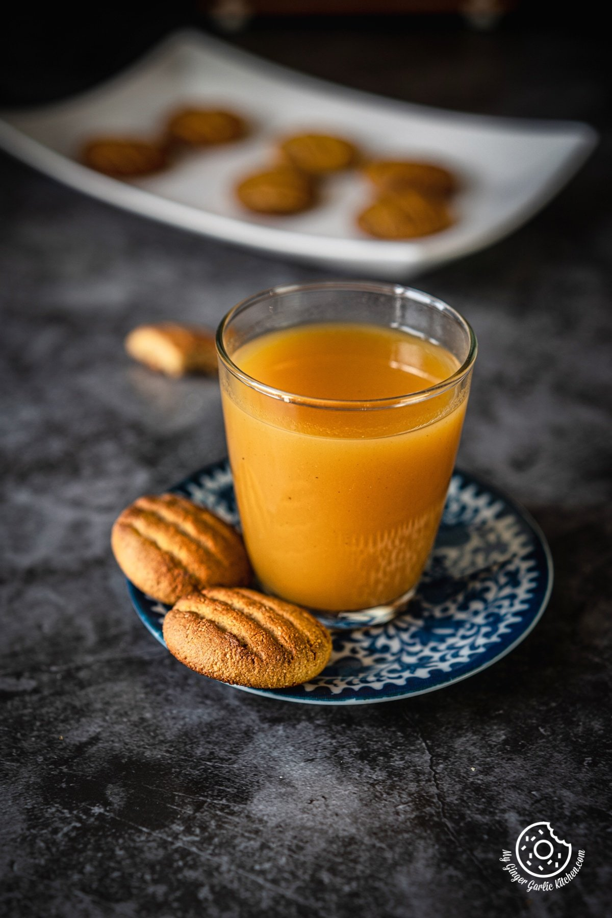 two almond flour cookies in a blue plate with a glass of orange juice