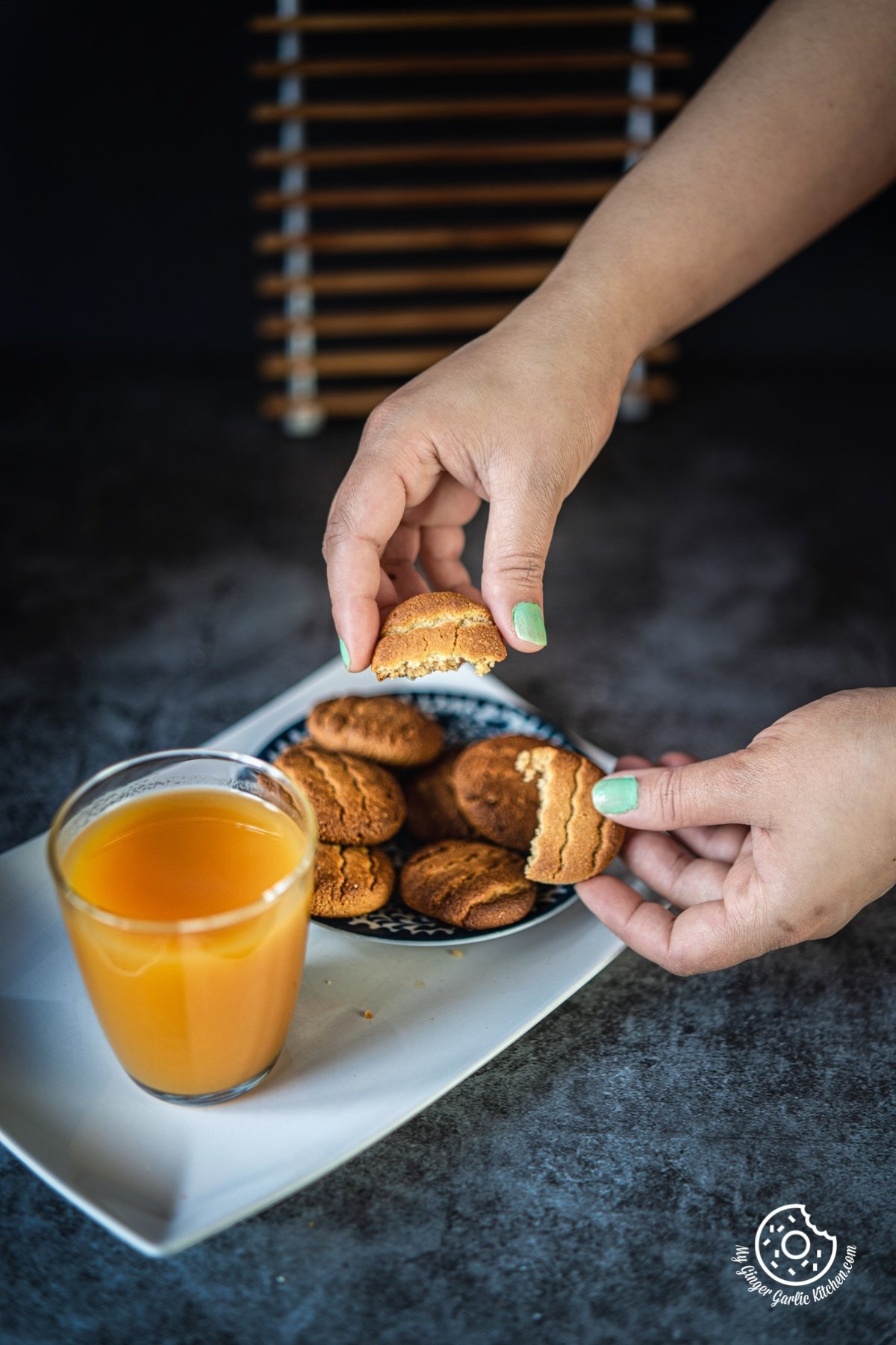 two hands holding two halve pieces of almond flour cookies with cookie plate and a juice glass