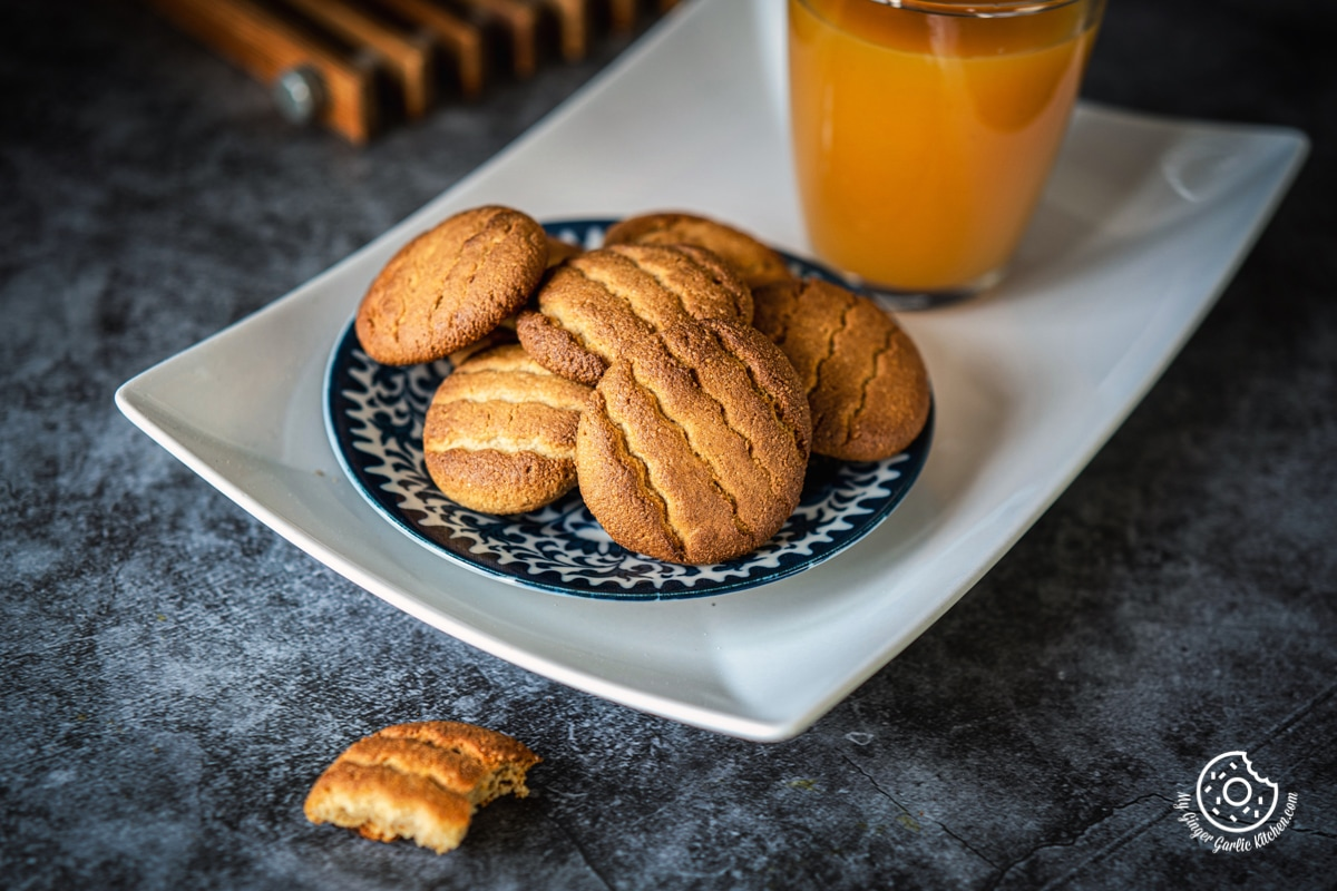 almond flour cookies in a blue plate with a glass of orange juice