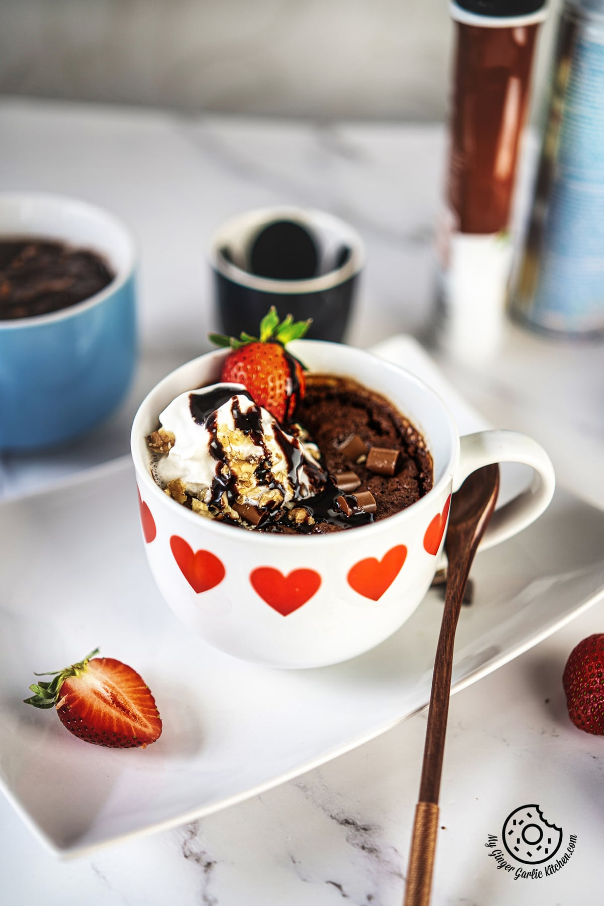 chocolate brownie in a white ceramic mug topped with whipped cream and strawberry