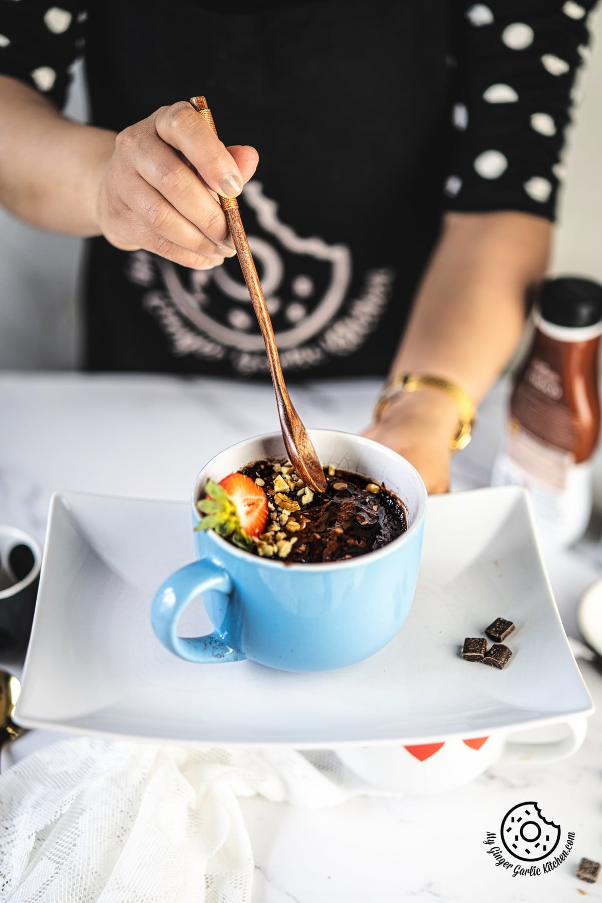 a female holding a wooden spoon over a chocolate brownie mug topped strawberry