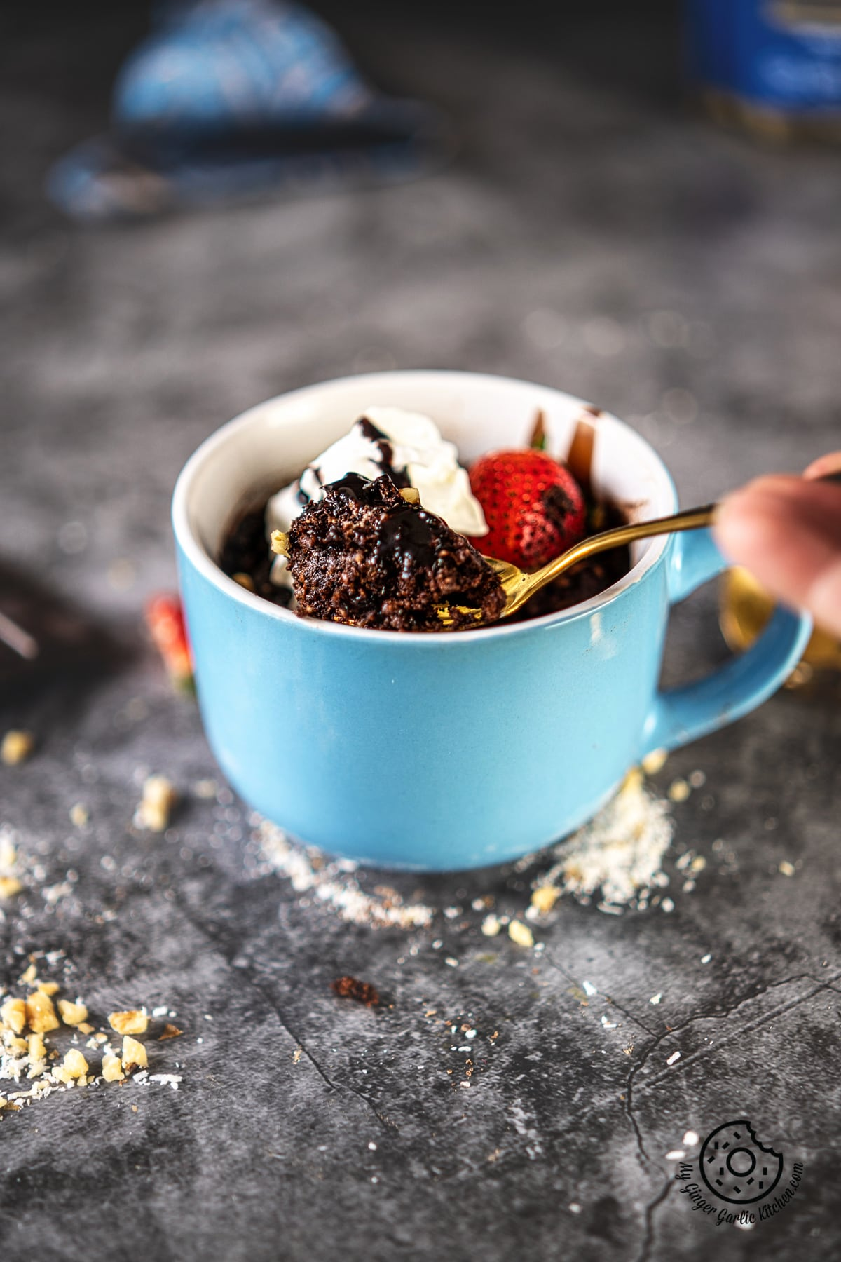 a hand holding a golden spoon over a chocolate brownie mug