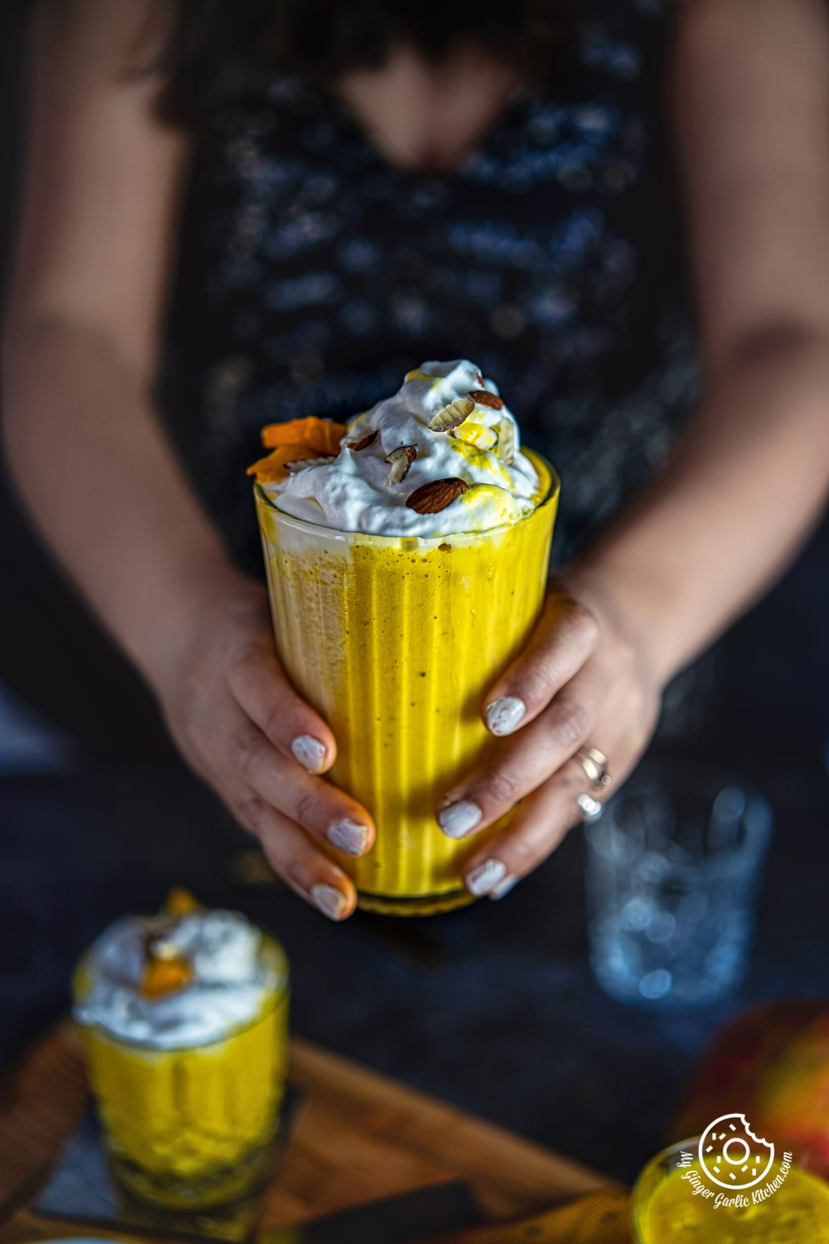 a female holding a tall glass of mango milkshake topped with whipped cream and nuts