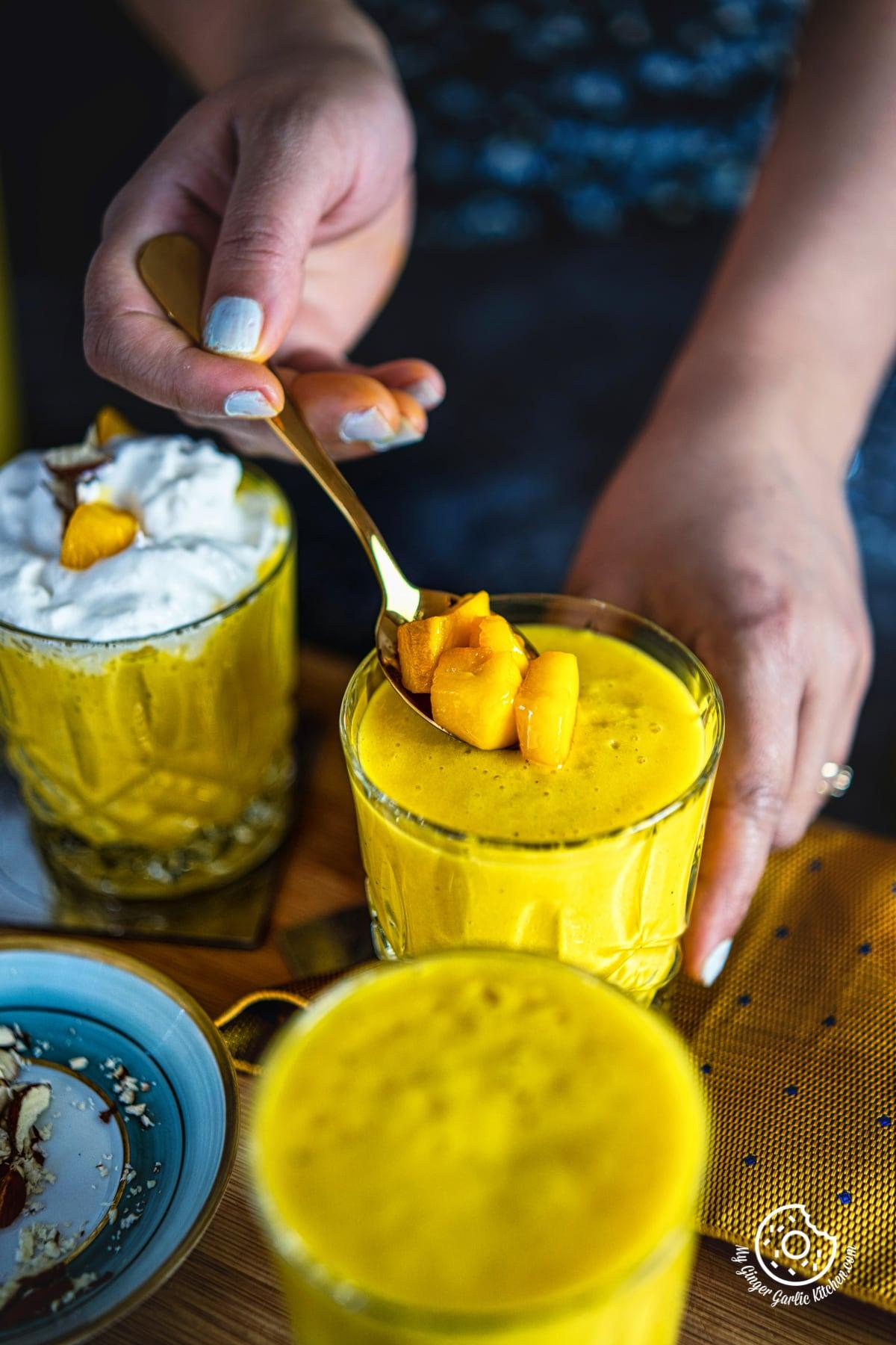 a female hand holding a spoon with chopped mangoes on a mango milkshake glass
