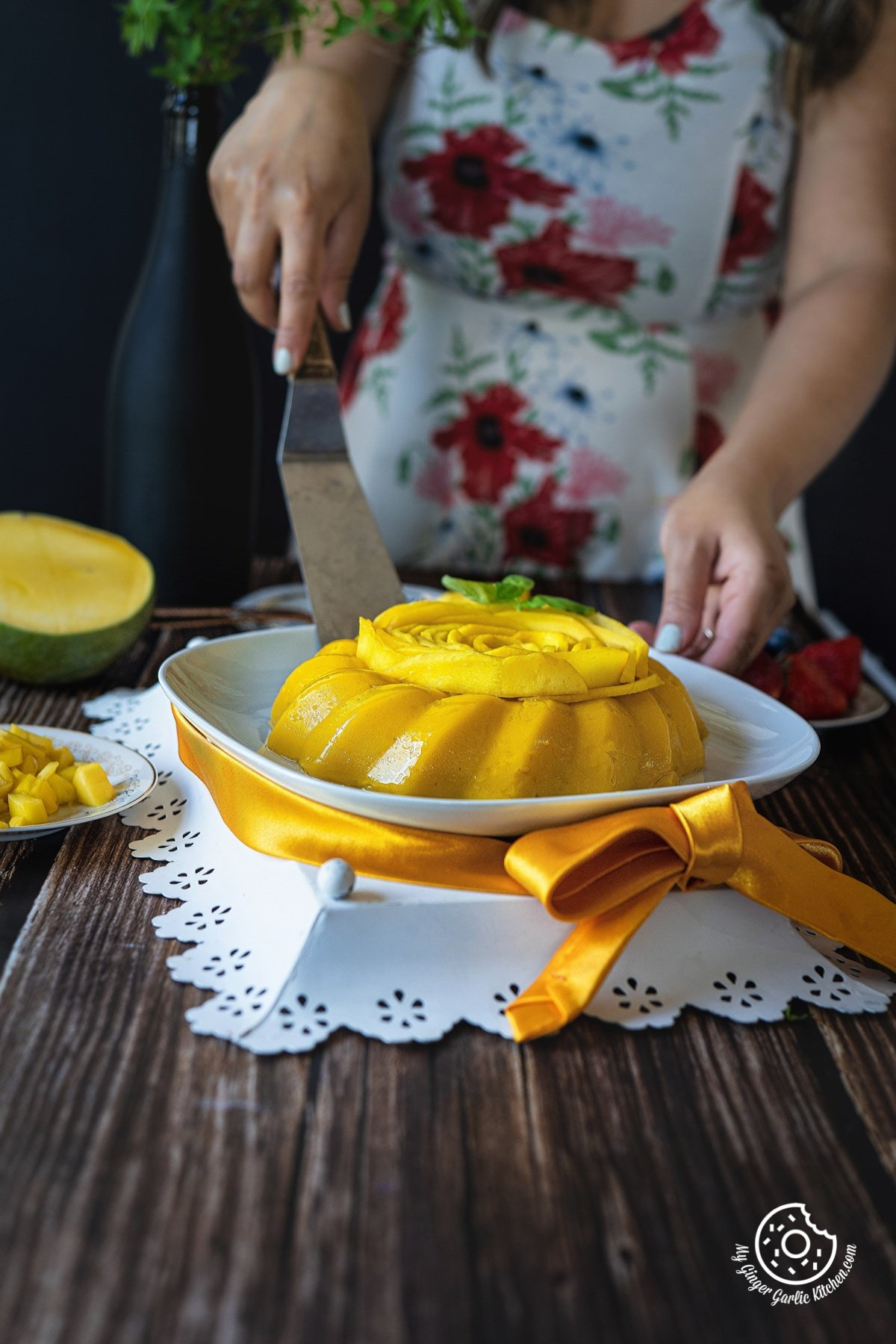 a female is holding a cake lifting spatula with one hand and holding mango pudding plate with the other hand