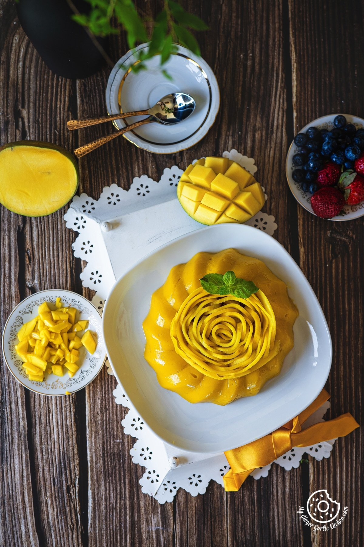 overhead shot of mango pudding in a white plate with some chopped mangoes and a half mango kept on the side