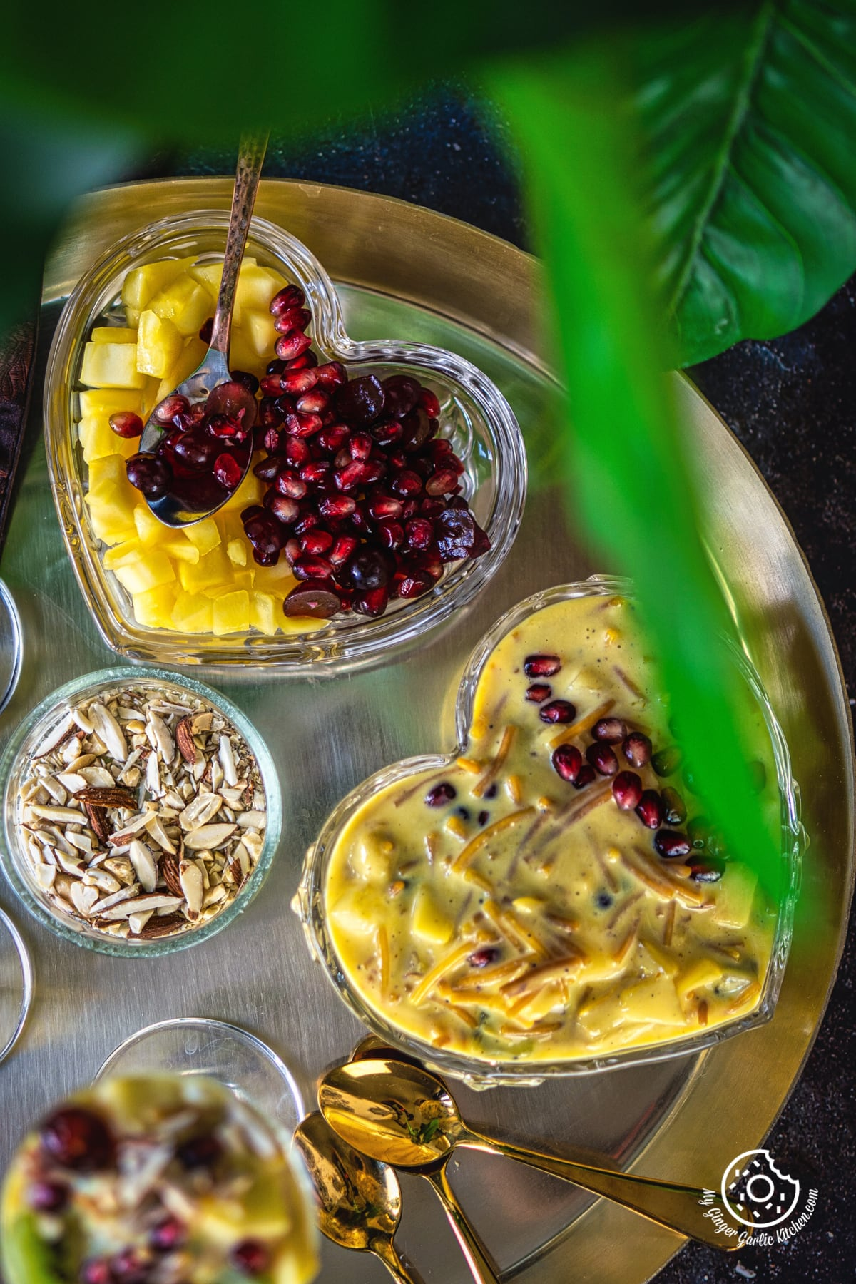 overhead shot of vermicelli fruit custard bowl in a golden plate along with a fruit plate