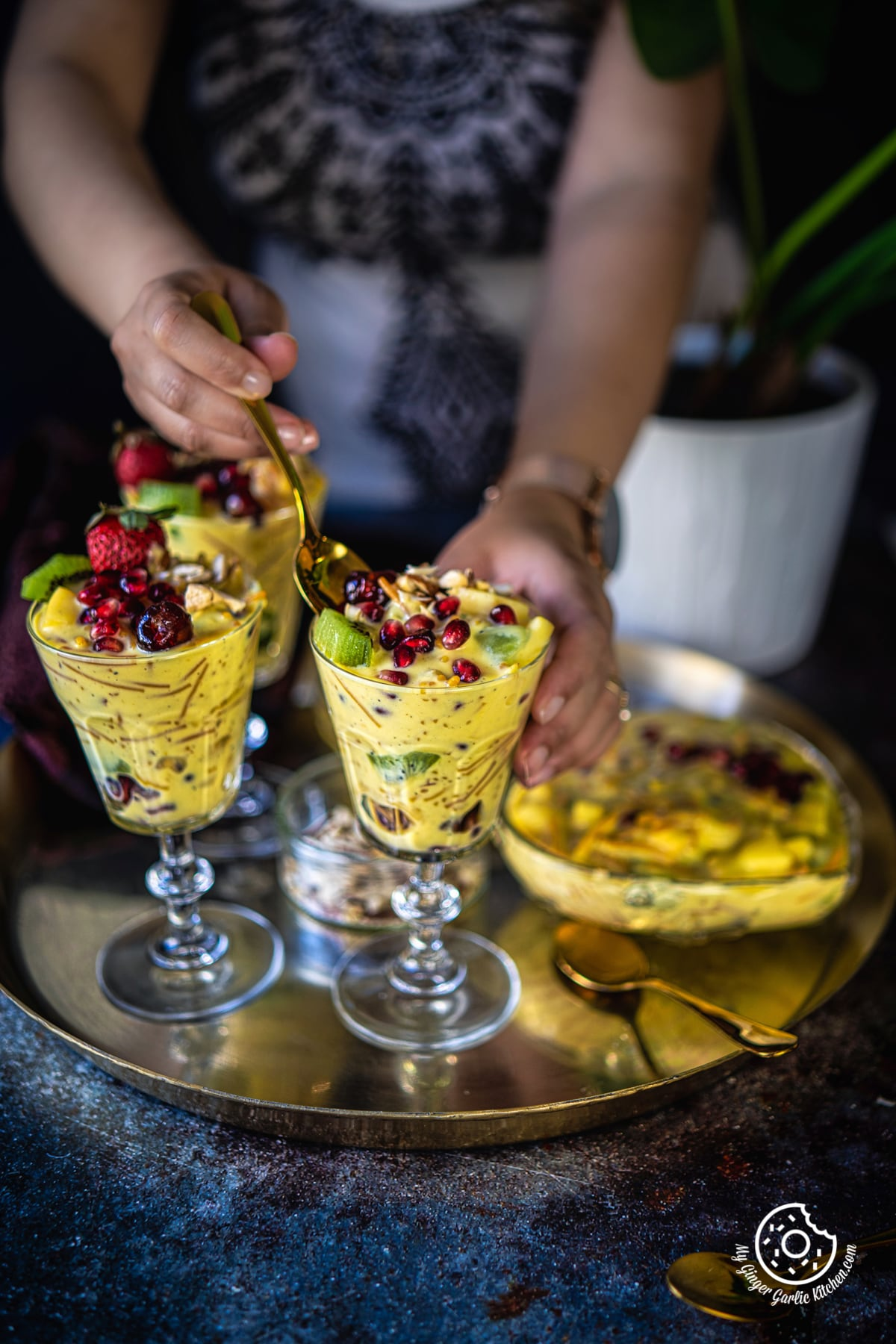 a female holding a golden spoon over a vermicelli fruit custard glass