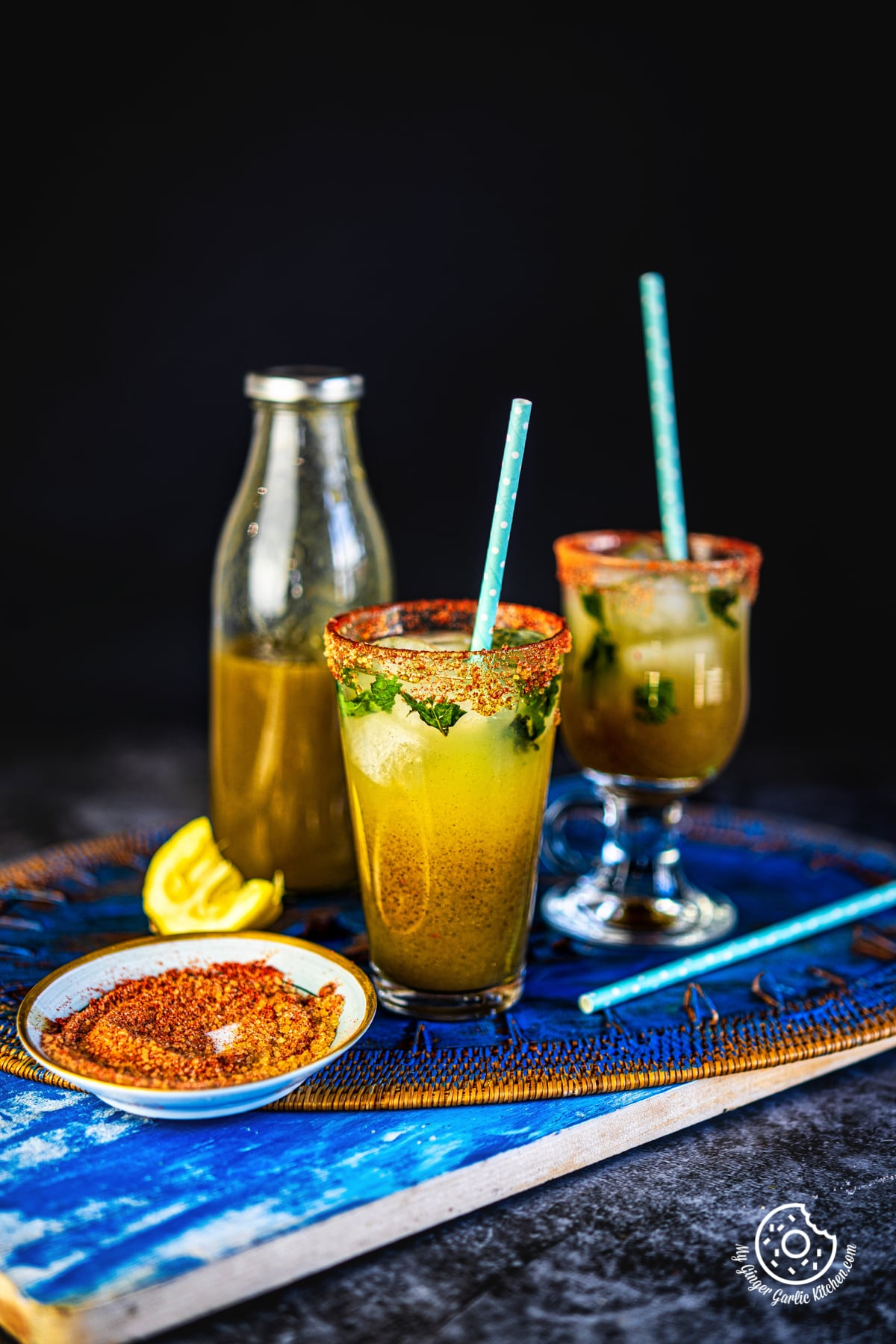 two glasses of aam panna with a aam panna bottle in the background