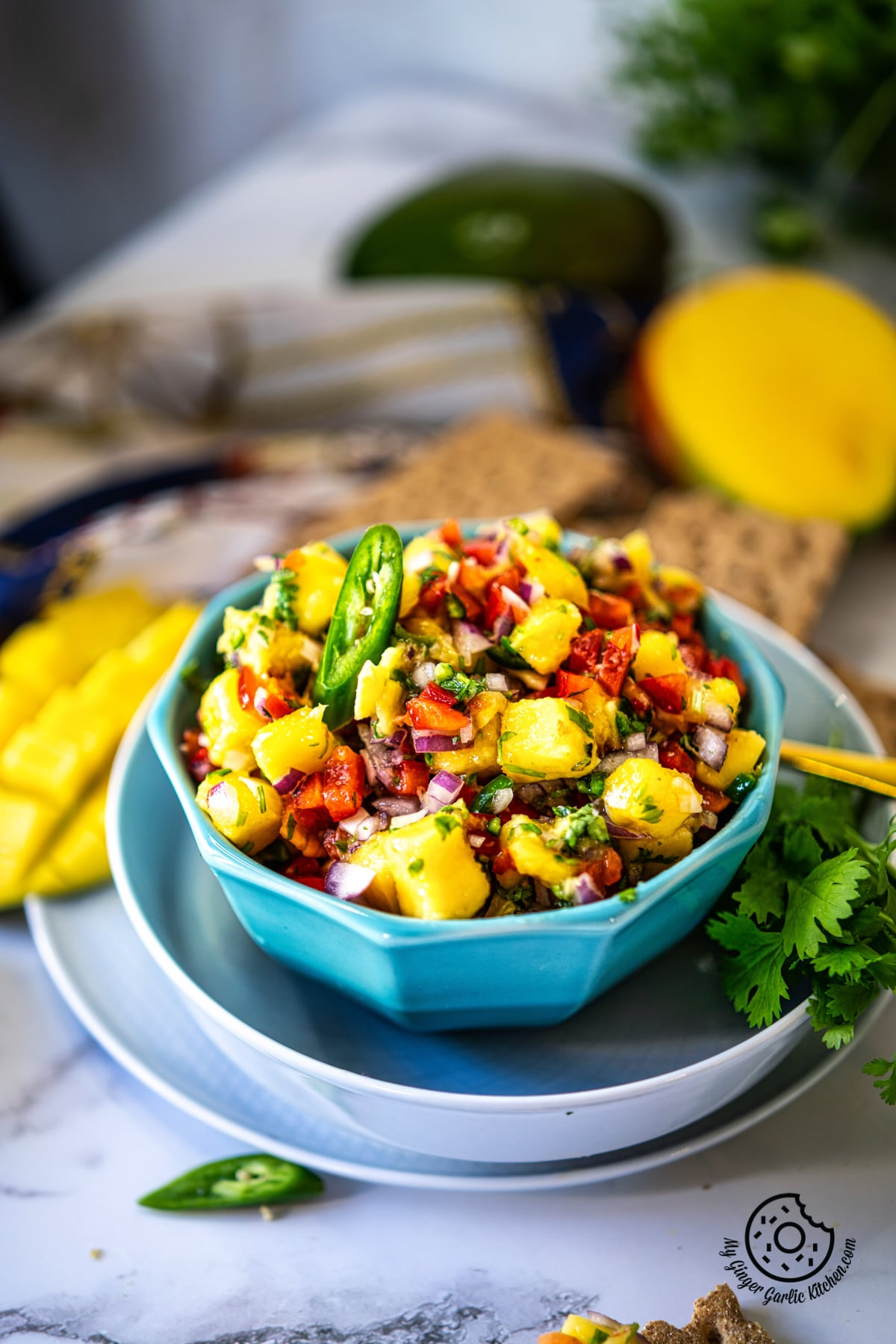 a blue bowl of mango salsa kept on a white marble background