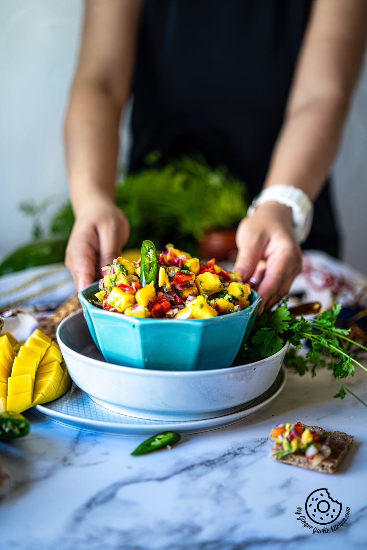 a female holding a light blue mango salsa bowl