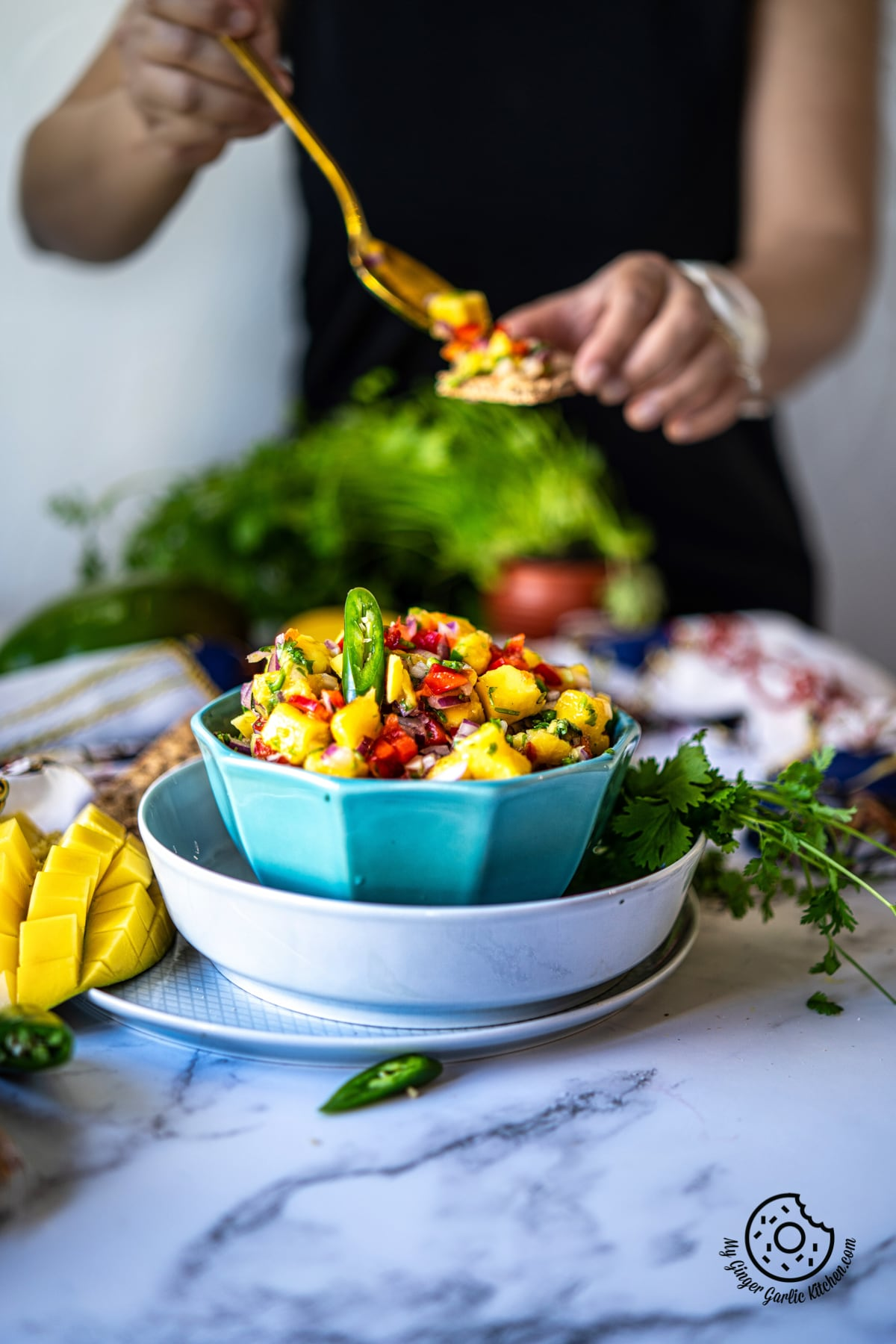 a light blue mango salsa bowl and a female in the background