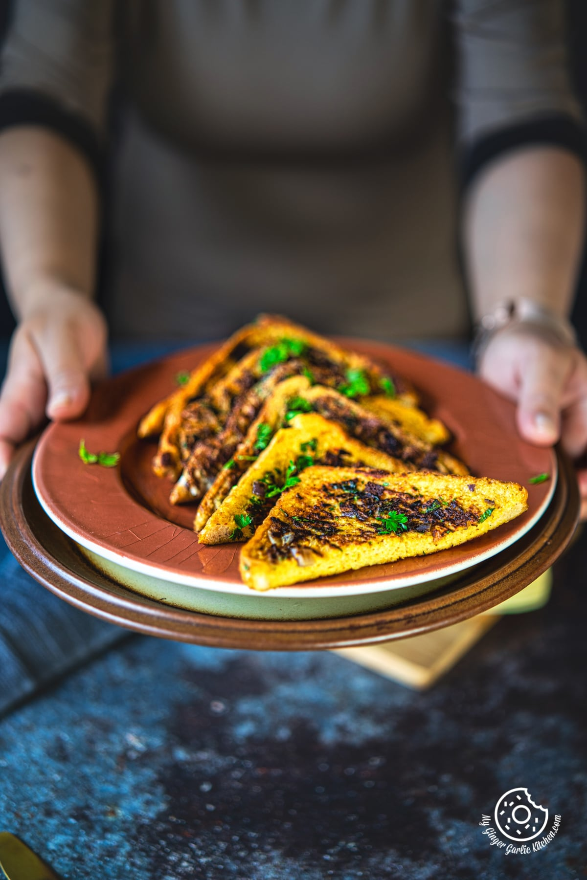 a female holing a plate with masala french toast
