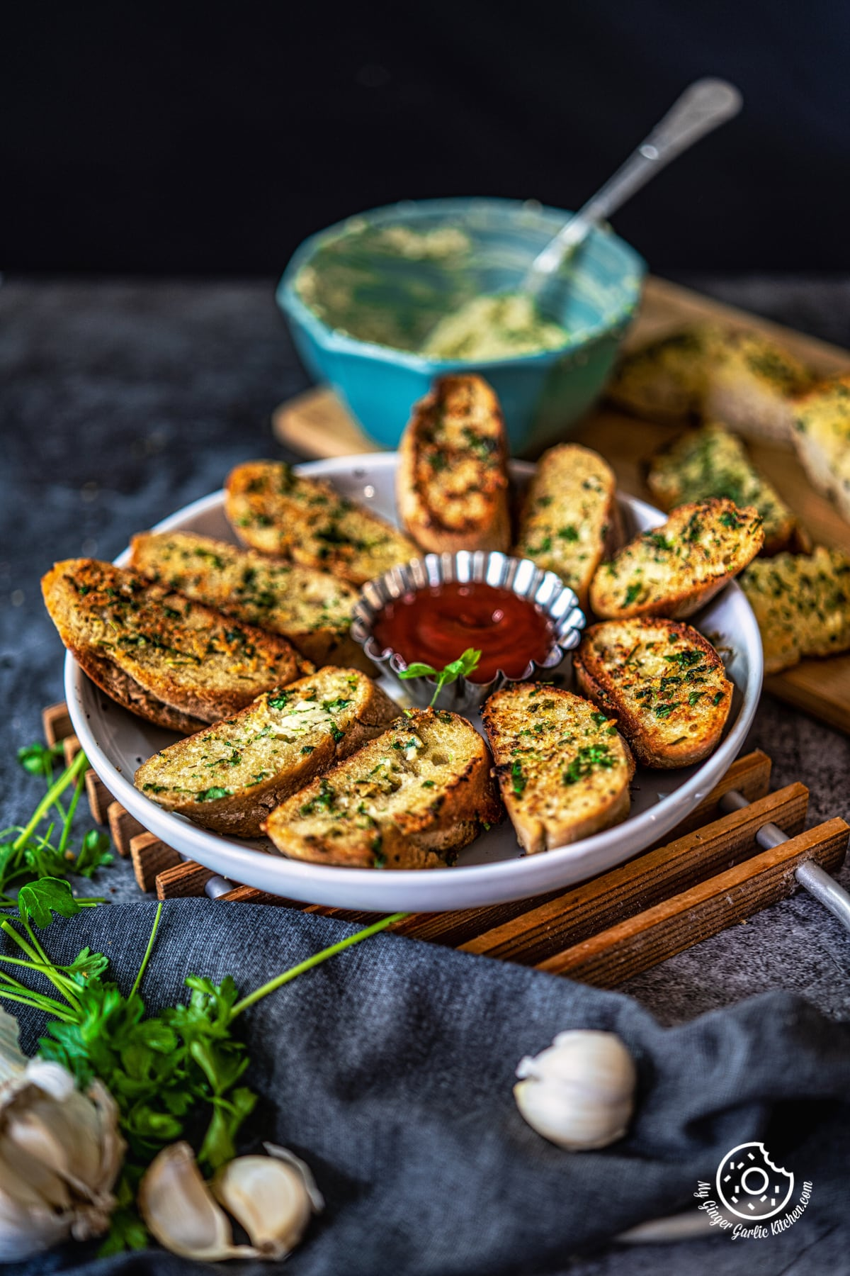 garlic bread in white plate along with a ketchup bowl