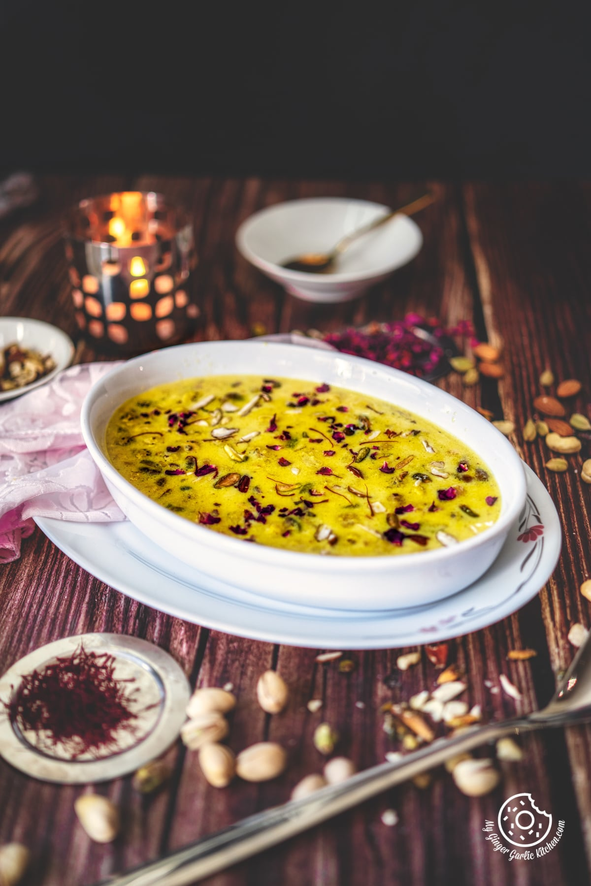 makhana kheer in a white oval shaped bowl and a candle in the background