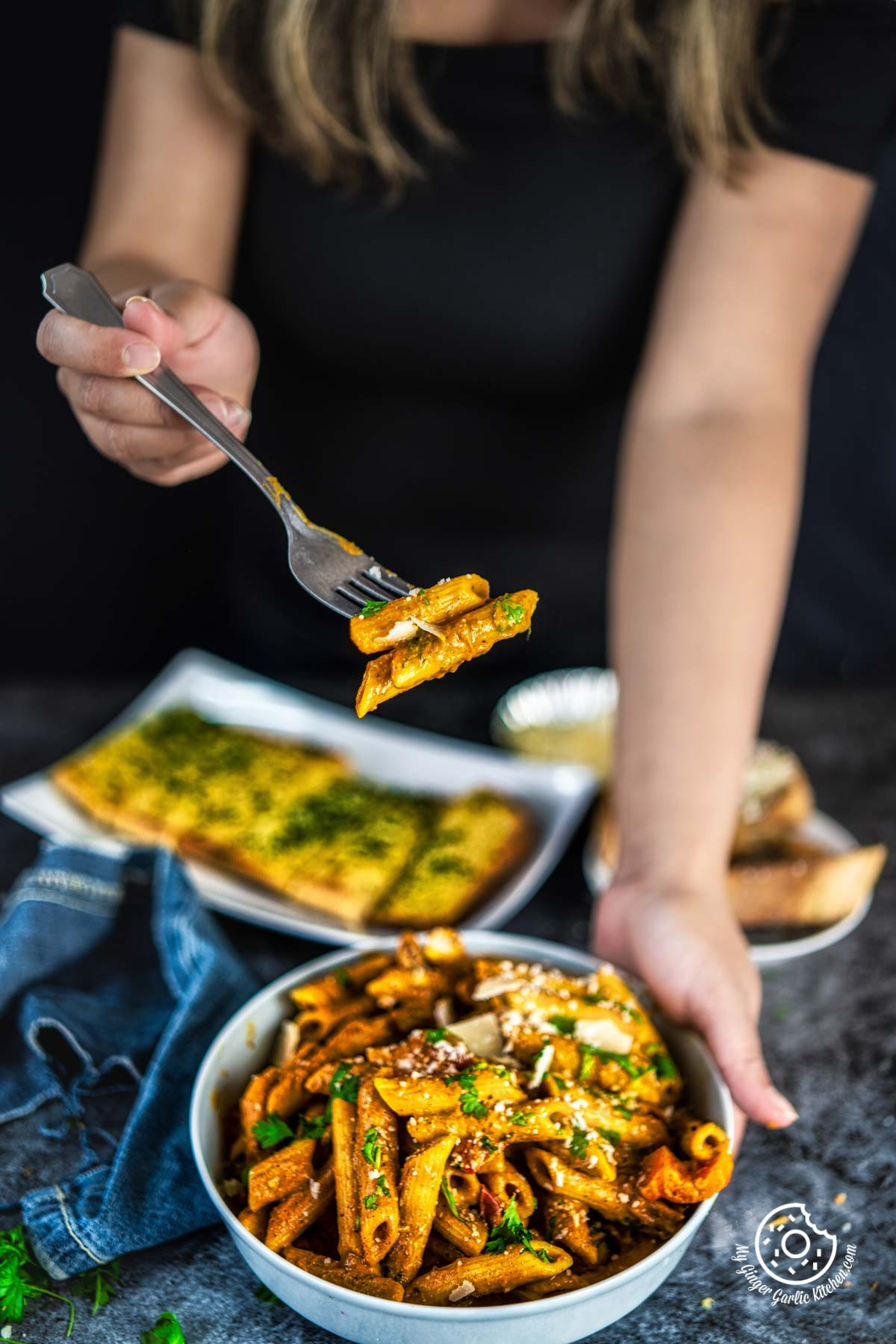 a female holding a fork with delicious creamy makhani sauce pasta