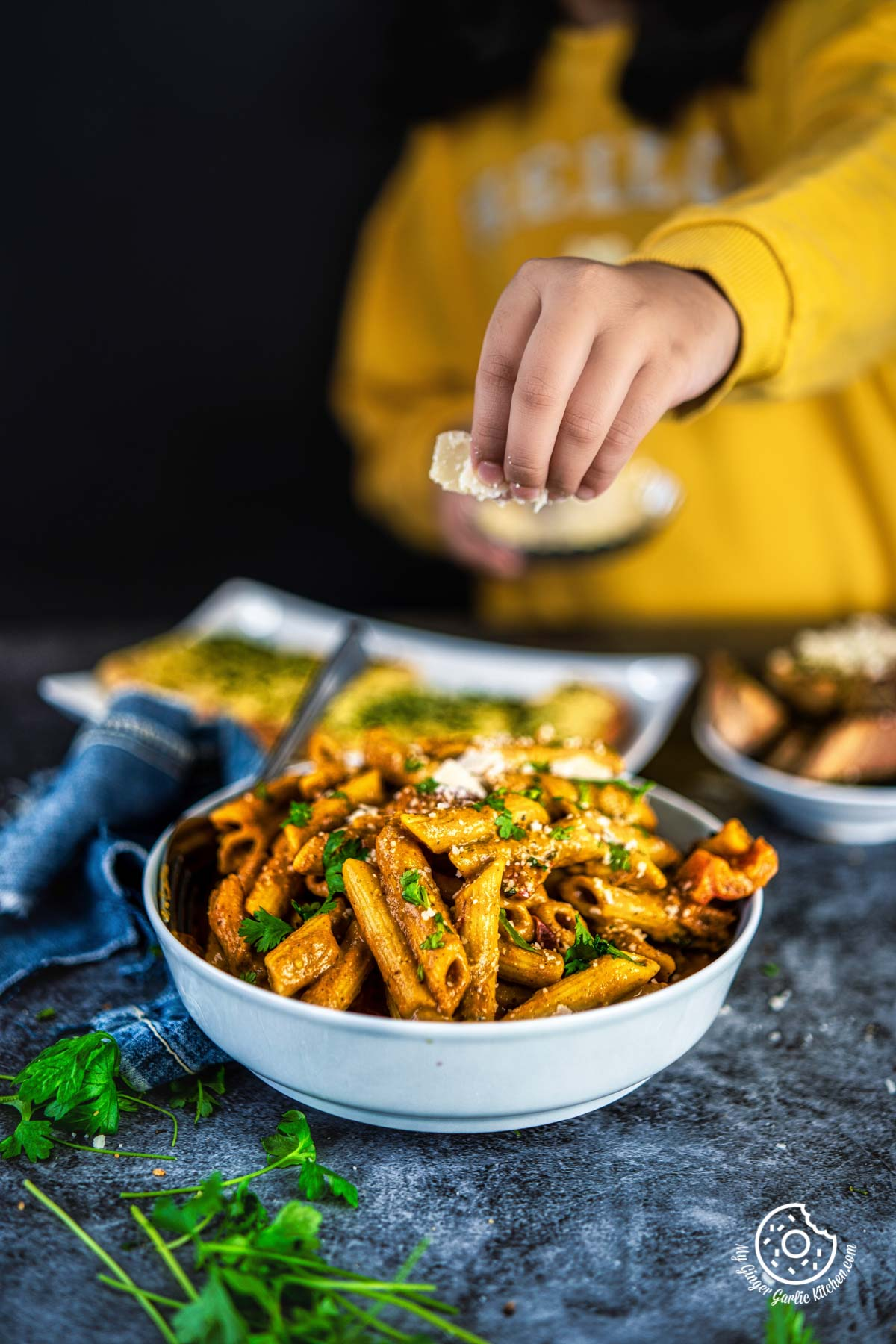 a hand holding cheese flakes over a delicious makhani pasta bowl