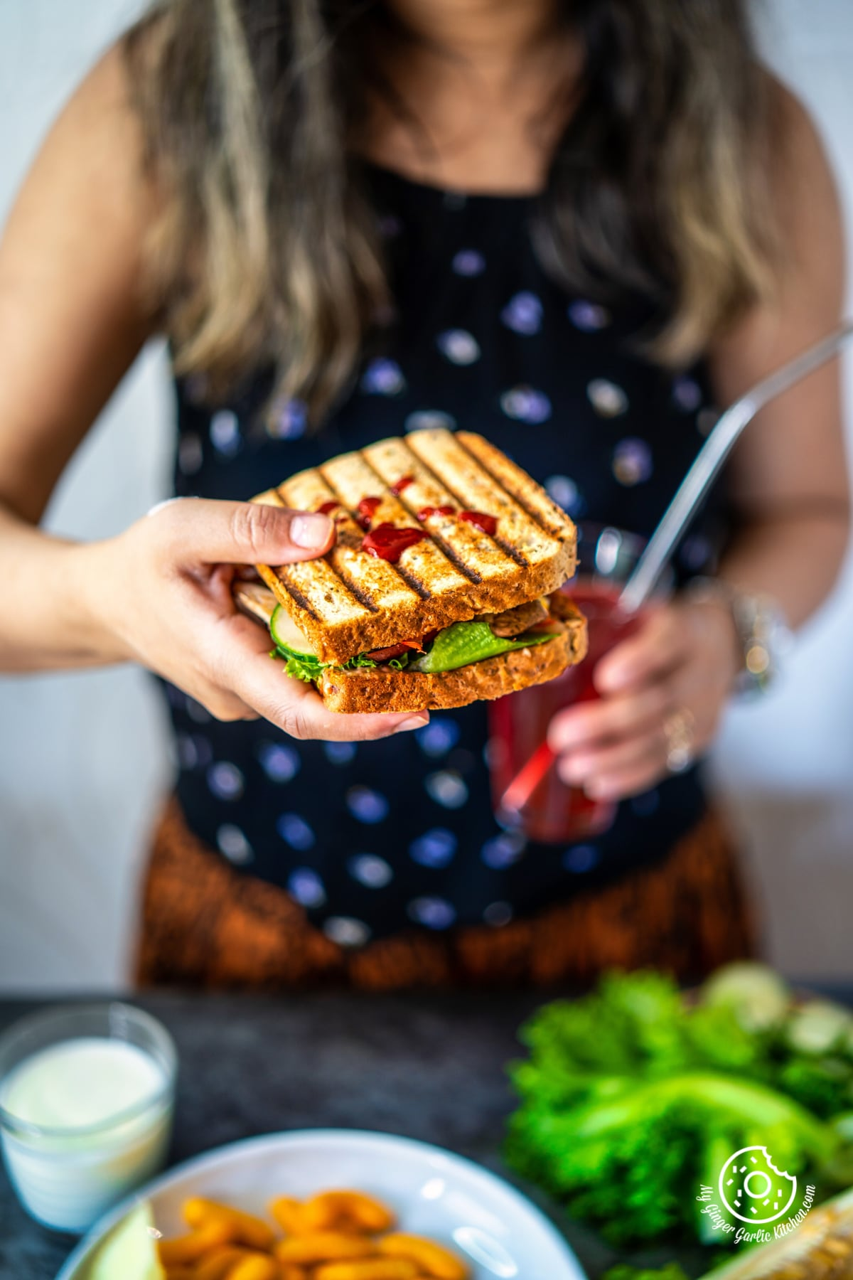 a female holding peanut butter and veggie grilled cheese sandwich