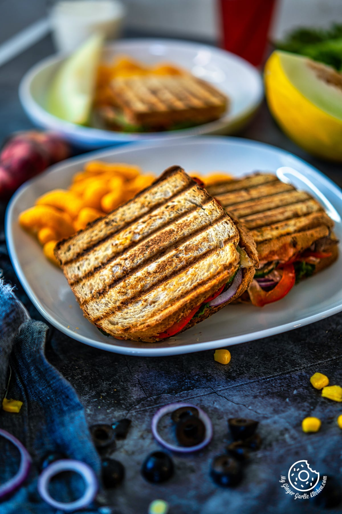 peanut butter and veggie grilled cheese sandwiches in a white plate along with cheese puffs
