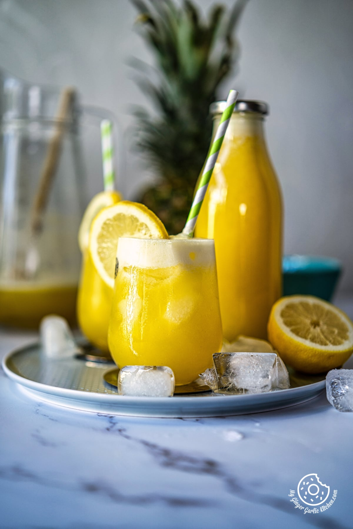 pineapple juice glass topped with a lemon slice and a bottle in the background