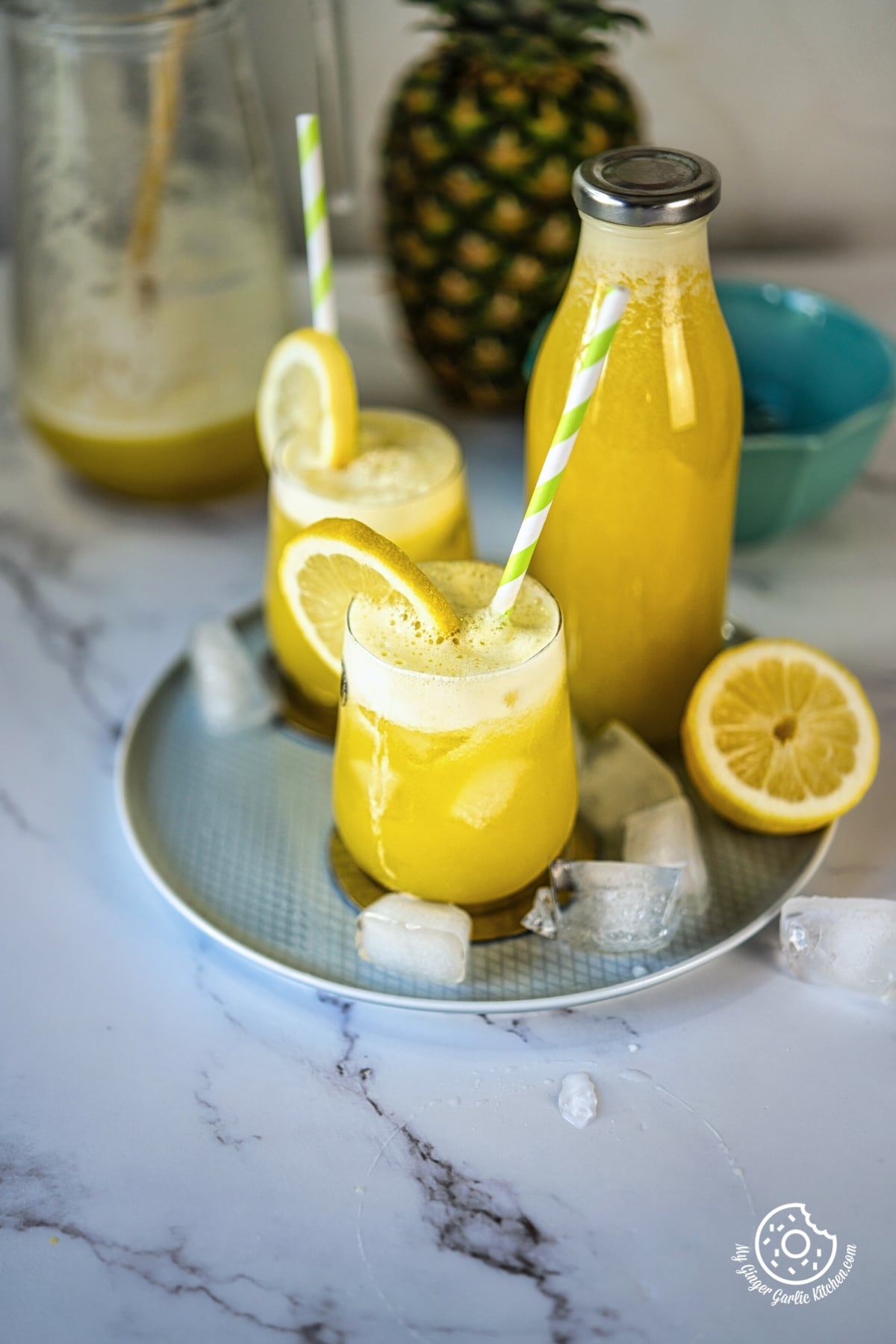 two pineapple juice glasses in a plate with half lemon and ice cubes