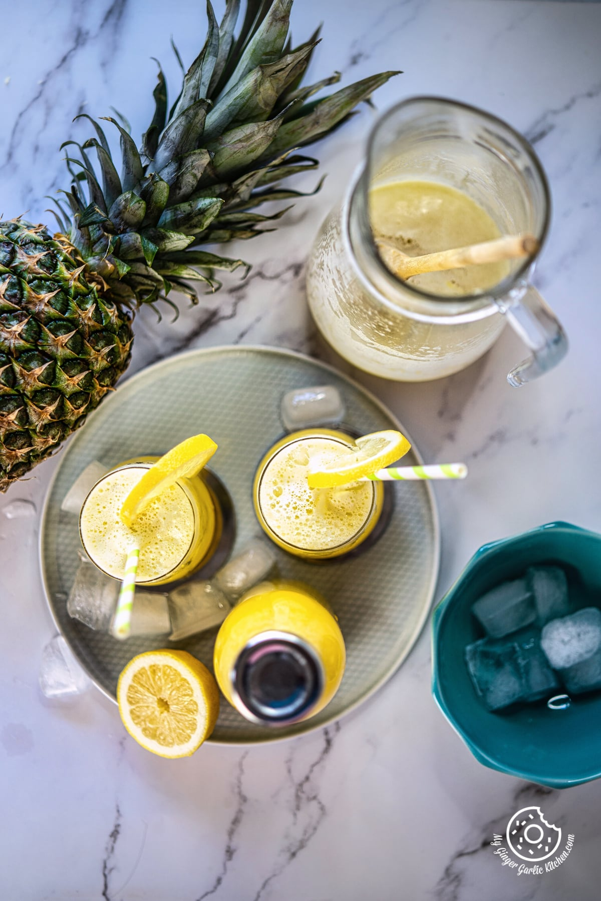 overhead shot of two pineapple juice glasses and a bottle in a plate and a pineapple and pitcher on the side