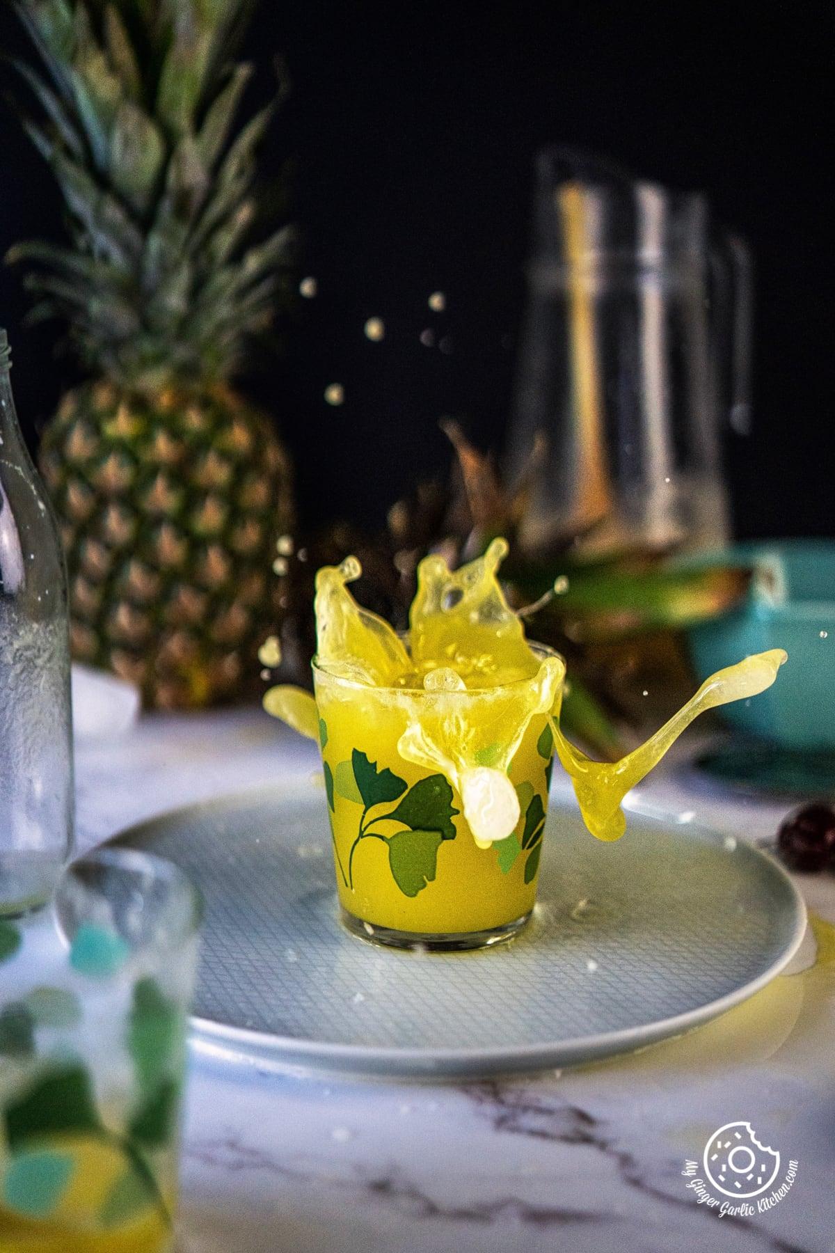 Pineapple juice splashing from a glass
