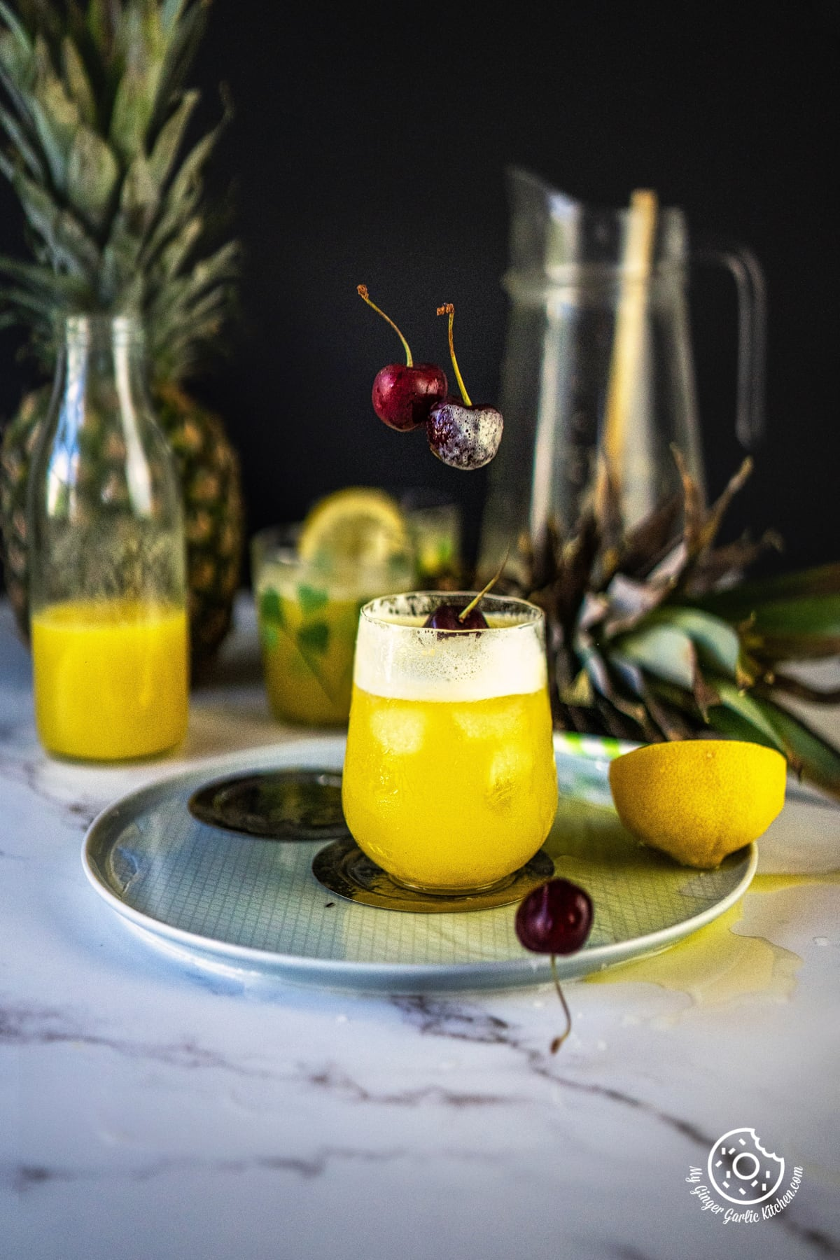 pineapple juice in a plate with a cherry and lemon on the side