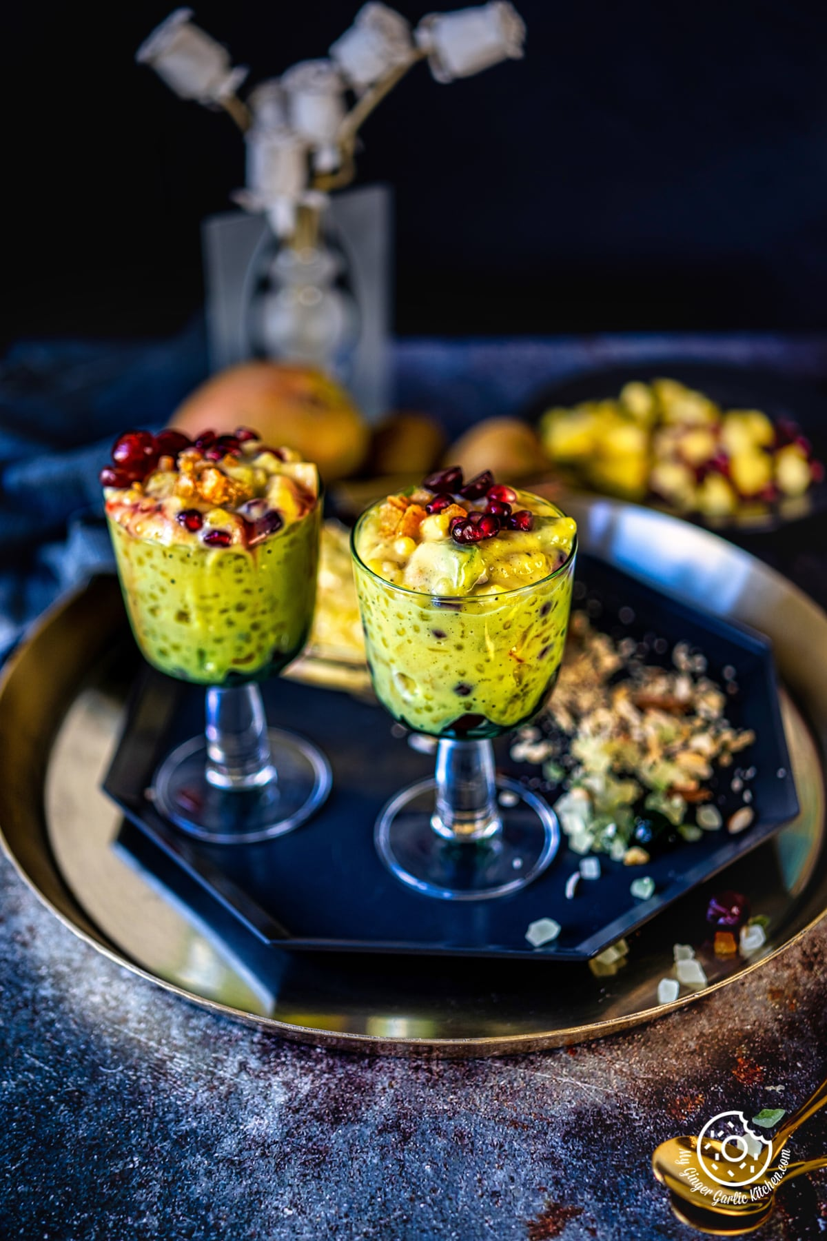 two sago fruit custard glasses on a metal plate and some chopped nuts on the side