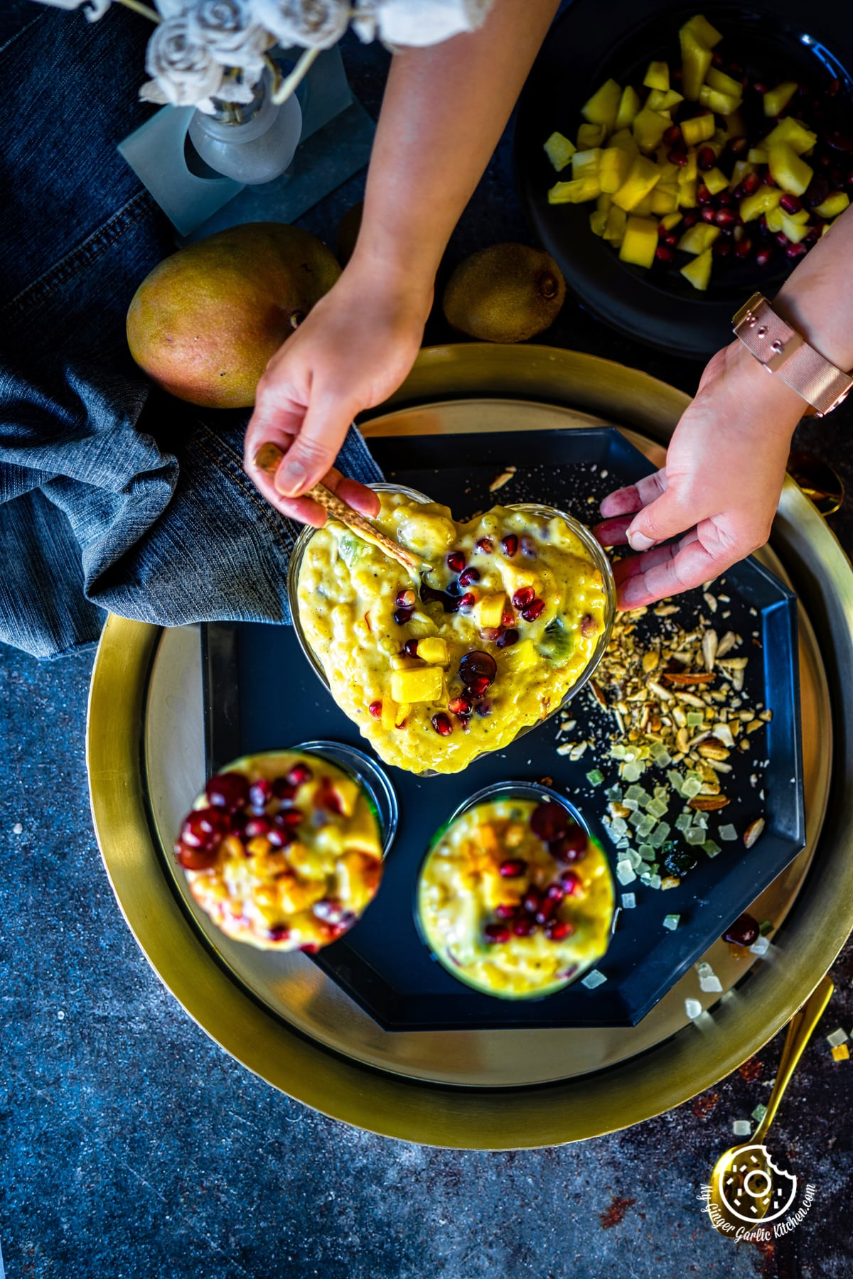 overhead shot of two hands holding a heart shaped sago fruit custard bowl and two glasses on the side
