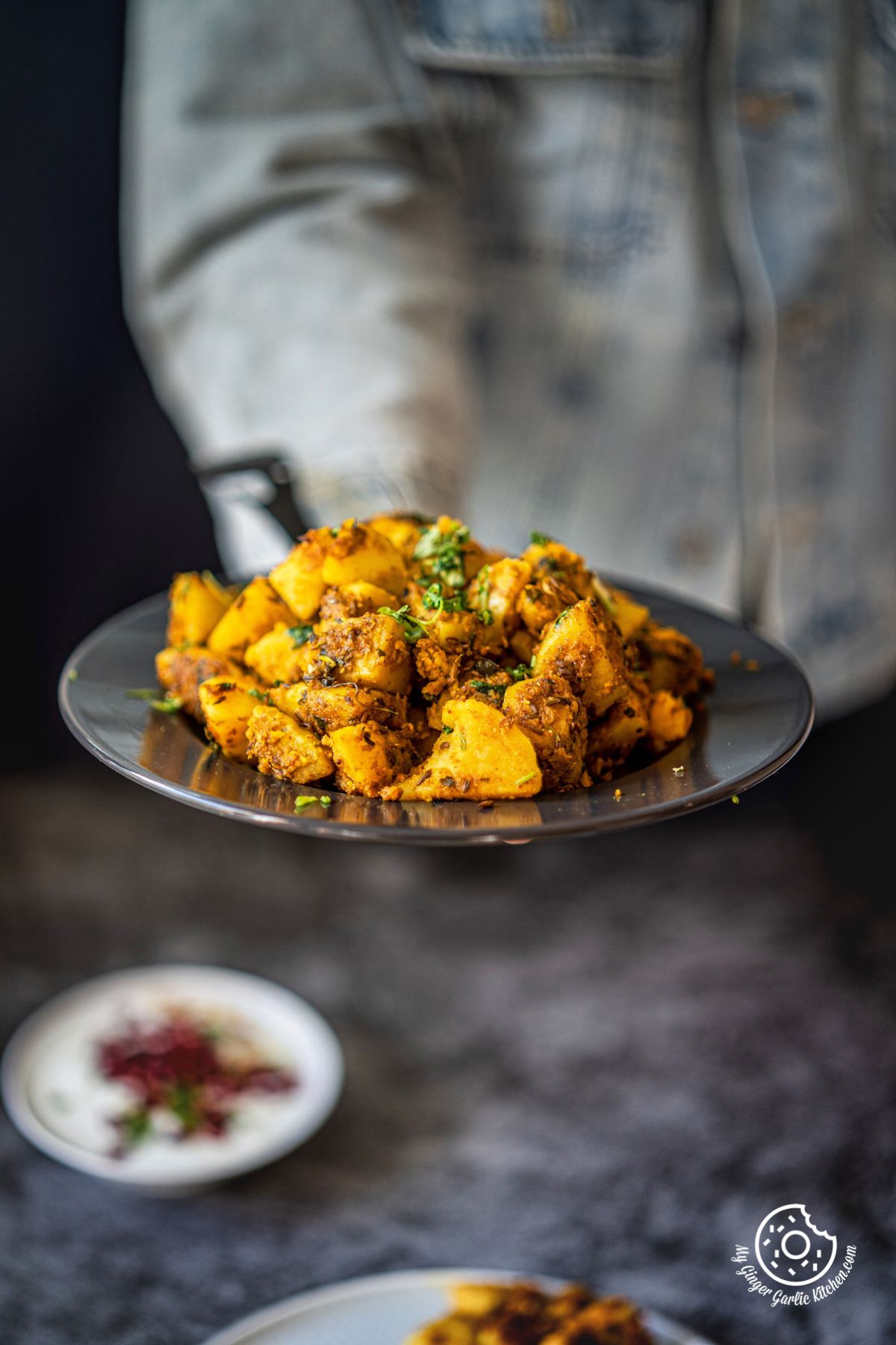 a man holding jeera aloo served in a grey ceramic plate