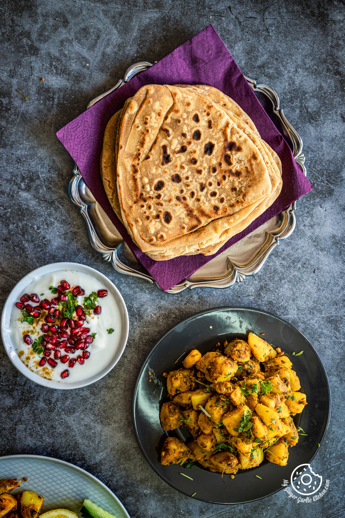 overhead shot of jeera aloo served in a grey plate with  pomegranate raita and parathas on the side