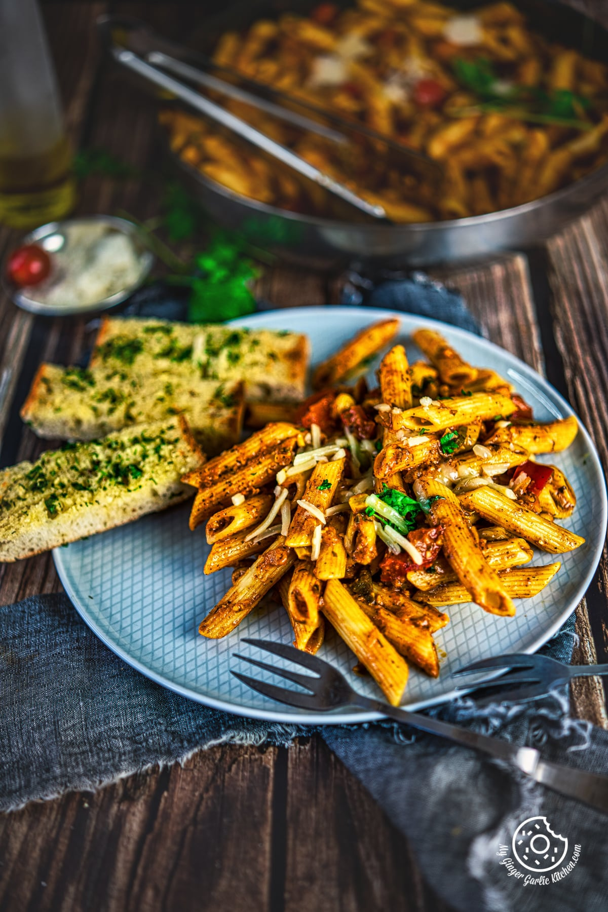 masala pasta served in a grey plate along with garlic bread sticks