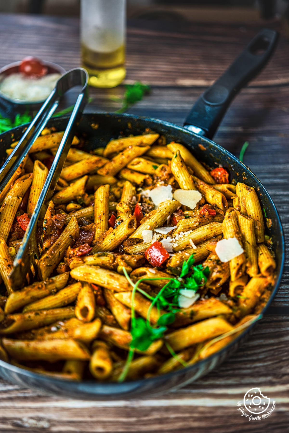 masala pasta in a black pan topped with cheese
