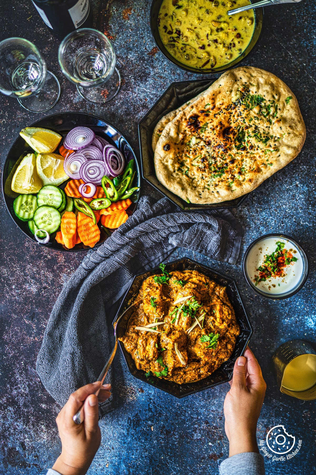 overhead shot of two hands holding paneer korma curry with some and salad on the side