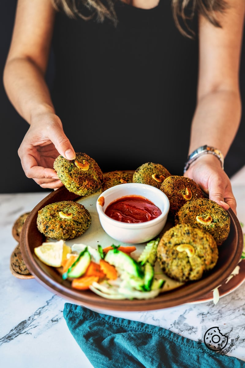 a female holding crispy hara bhara kababs plate with ketchup and salad