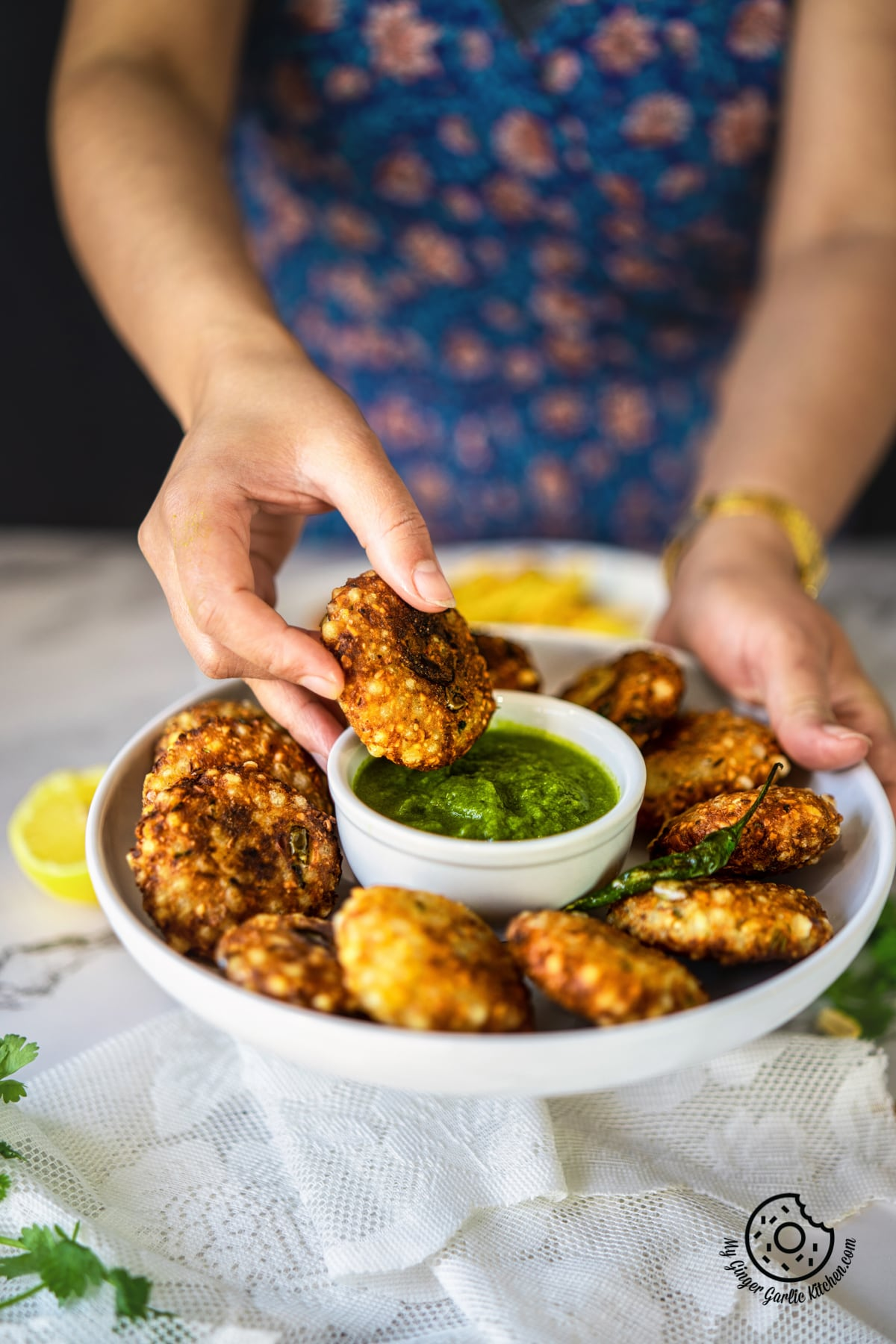 a female holding a sabudana vada over green chutney bowl kept in a white plate with more vadas